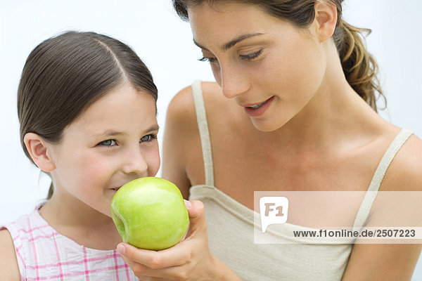 Mutter schenkt Tochter einen Apfel  beide lächelnd
