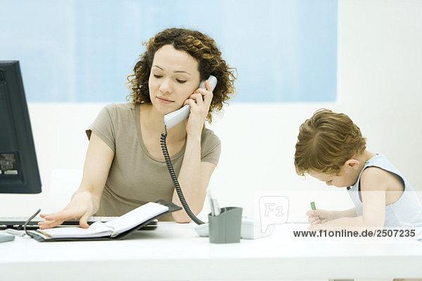 Frau mit Telefon und Blick auf die Tagesordnung  junger Sohn sitzt neben ihr  Färbung