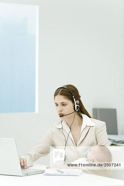 Professionelle Frau im Büro  Baby haltend  mit Headset und Laptop-Computer