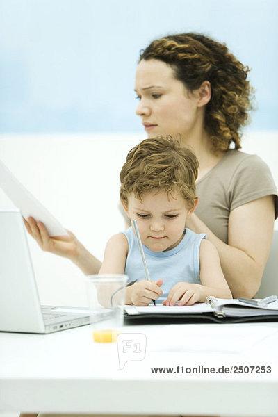 Mutter hält den Sohn auf dem Schoß  sitzt vor dem Laptop und runzelt die Stirn.