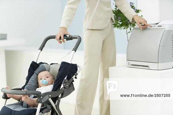 Professionelle Frau im Büro mit Baby im Kinderwagen  mit Drucker  zugeschnittene Ansicht