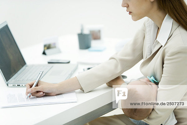 Junge berufstätige Frau im Amt  die ein schlafendes Kind hält  Unterschriftendokument