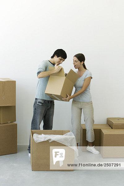 Paar auspacken  Mann zeigt Inhalt einer Schachtel  Frauenmund überrascht offen