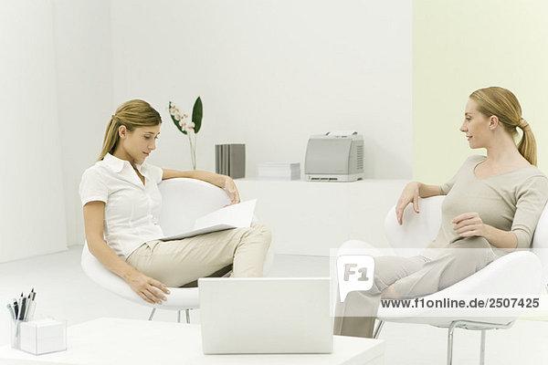 Zwei Frauen sitzen zusammen in casual Office  Lächeln  eine Lesung Dokument