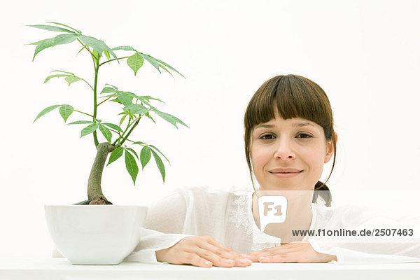 Frau sitzt mit Topfpflanze  Lächeln in die Kamera Frau sitzt mit Topfpflanze, Lächeln in die Kamera