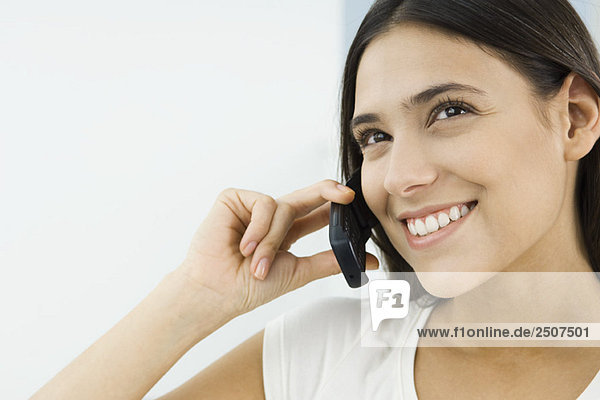 Woman using cell phone  looking up and smiling