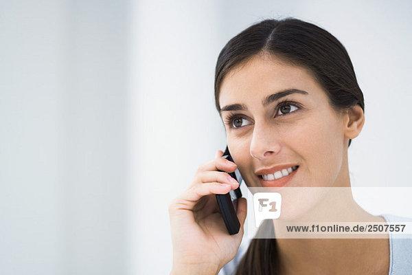 Frau Gespräch auf Handy  lächelnd und wegsehen