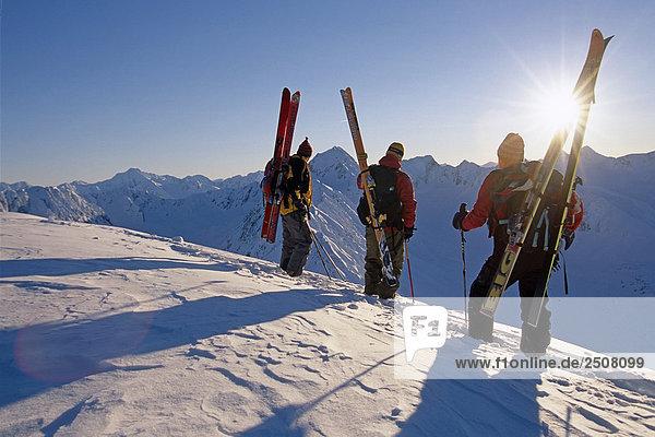 3 Extremskifahrer stehen auf Ridge mit Blick auf Turnagain Arm Chugach CT in South Central Alaska Winter sun