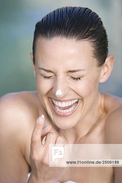 Junge Frau mit Gesichtscreme  Portrait  Lachen  Portrait