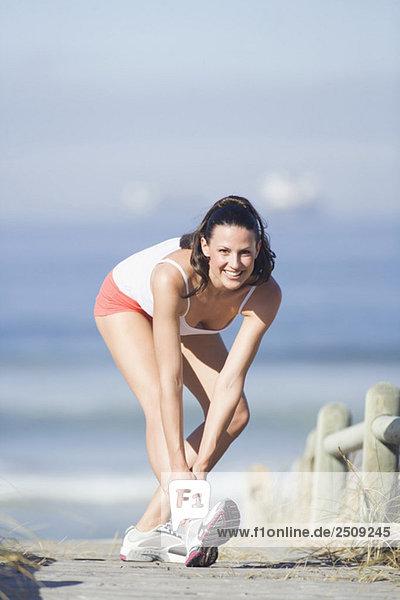 Junge Frau streckt Bein  lächelnd  Portrait