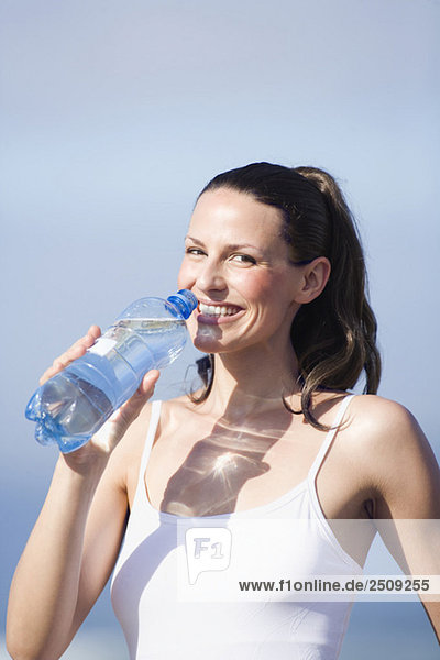 Junge Frau trinkt Wasser  Porträt