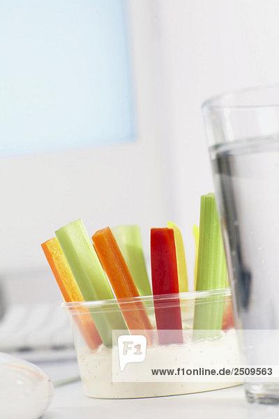 Kunststoffschale mit Gemüsestäbchen und Dip auf dem Schreibtisch