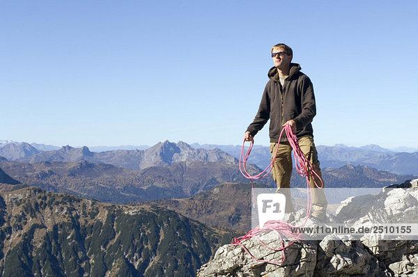 Österreich  Salzburger Land  Junger Mann mit Seil gegen die Bergwelt