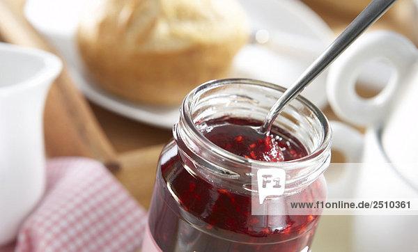 Frühstück  Nahaufnahme des Löffels in einem Glas Marmelade