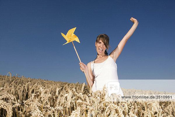 Junge Frau im Feld stehend  Pinwheel haltend  Porträt