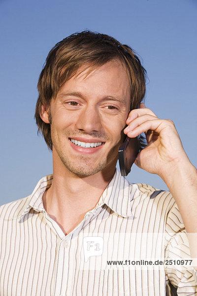 Junger Mann mit Handy  lächelnd  Portrait