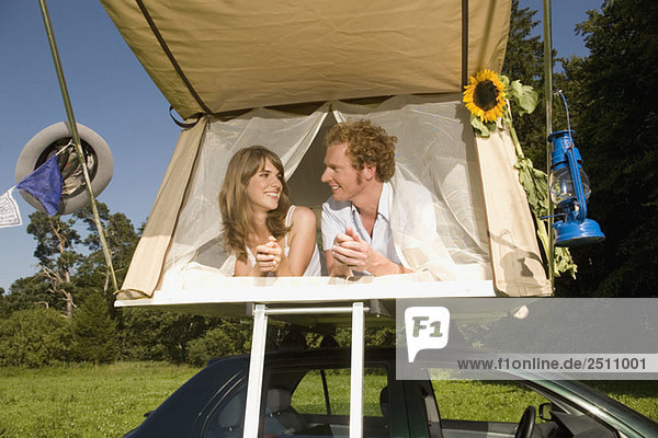 Germany  Bavaria  Young couple laying in tent