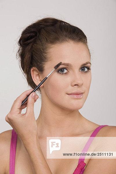 Junge Frau mit Augenbrauenstift  Portrait