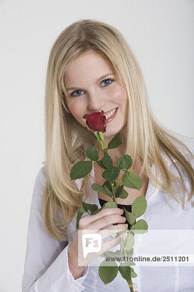 Junge Frau mit einer Rose  lächelnd  Portrait
