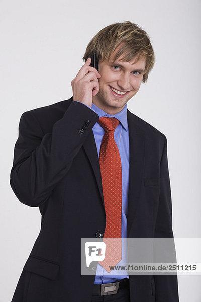Junger Geschäftsmann mit dem Handy  lächelnd