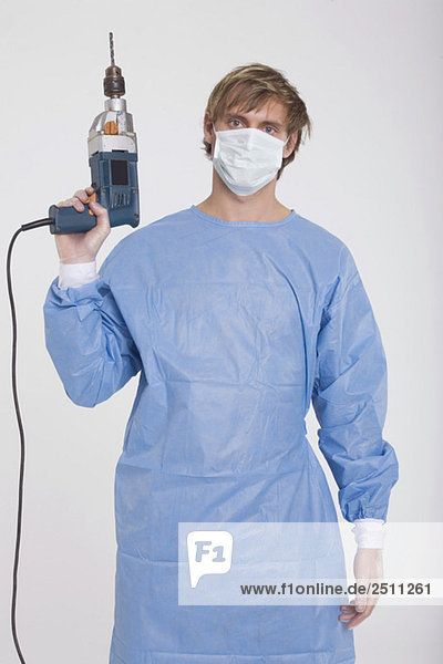Young doctor wearing a mask  holding power drill