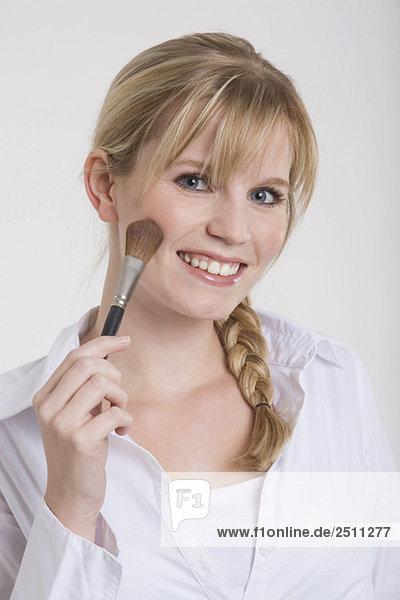 Junge Frau mit Schminkpinsel