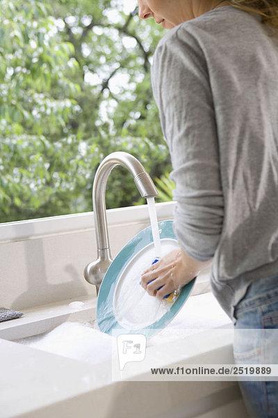 Frau wäscht Teller am Waschbecken
