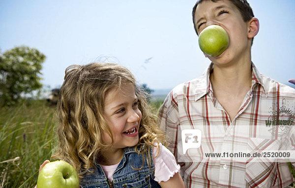 Junge hält Apfel in den Zähnen mit Mädchen