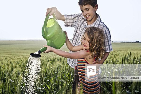 Junge hilft Mädchen mit Gießkanne
