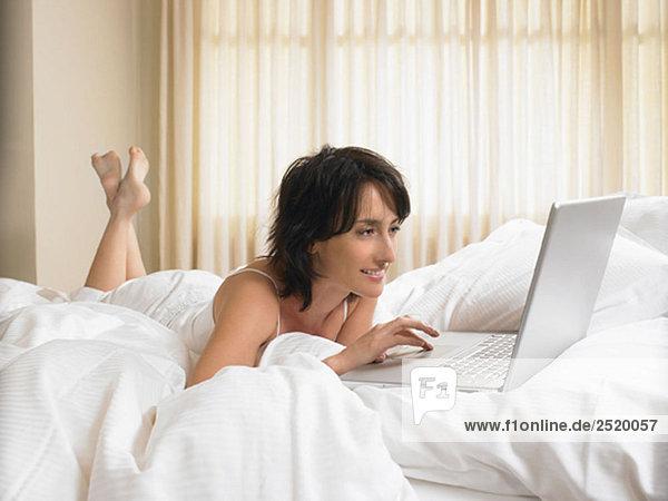 Frau im Bett mit Computer