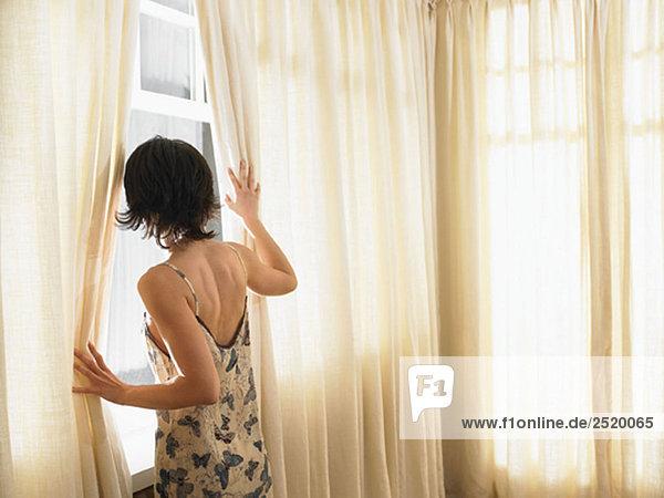 Frau schaut durchs Fenster