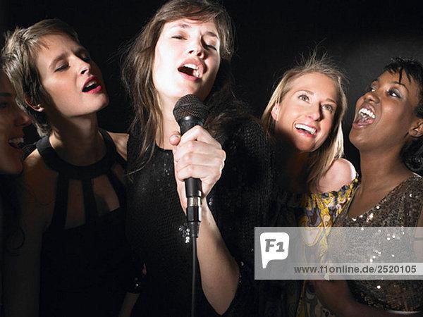 Gruppe von Frauen  die singen  Karaoke