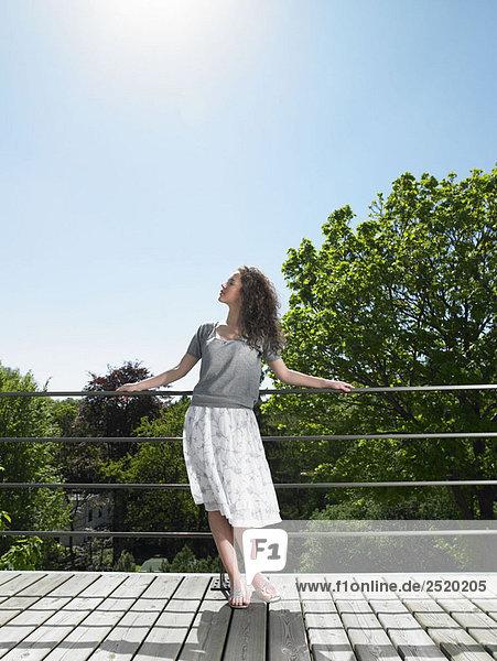 Frau genießt die Sonne auf der Terrasse