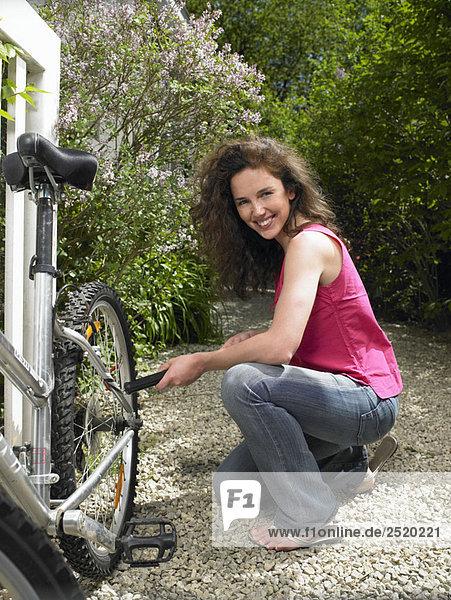 Frau pumpt ihr Fahrradrad auf