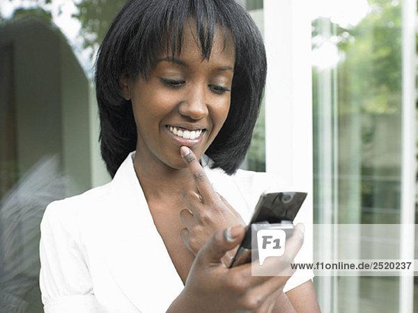 Frau schaut auf ihr Handy  lächelnd