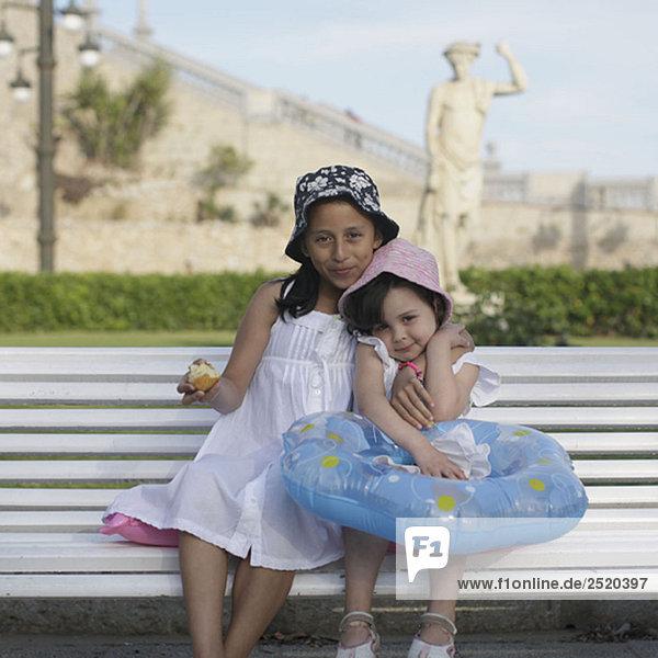 Zwei junge Mädchen sitzen auf der Bank