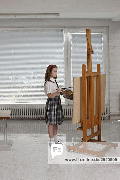 Junge Mädchen malen auf Staffelei