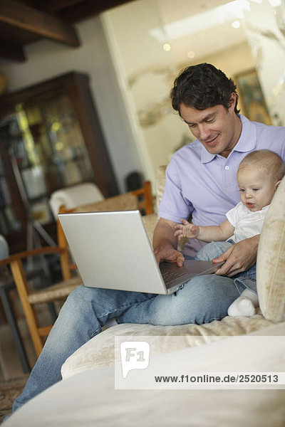 Vater sitzend am Laptop mit jungem Sohn