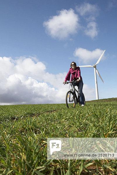 Frau beim Radfahren auf einem Windpark