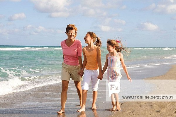 Mom walking with two young girls at beach