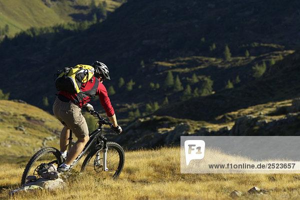 Mountainbikefahrer fährt einen Hang hinunter  fully_released