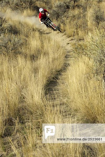 Downhillfahrer rast auf einem Pfad  fully_released