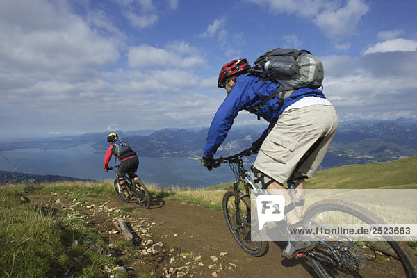 Two mountainbike riders driving down a path
