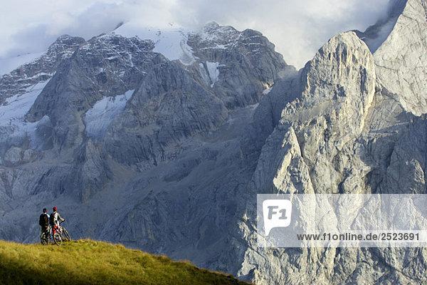 Zwei Mountainbikefahrer stehen vor einem felsigen Berg  fully_released