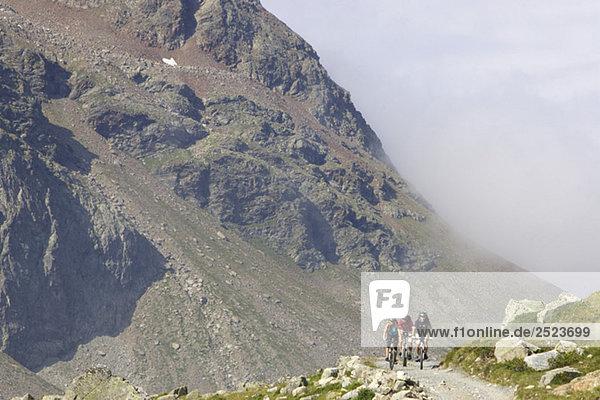 Drei Fahrradfahrer in einer Bergkulisse  fully_released