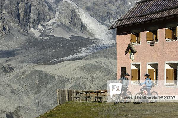 Zwei Mountainbikefahrer unterhalten sich vor einer Hütte  fully_released