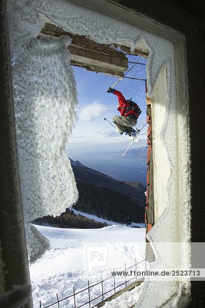 Skifahrer springt vor einem zerbrochenen Fenster  fully_released