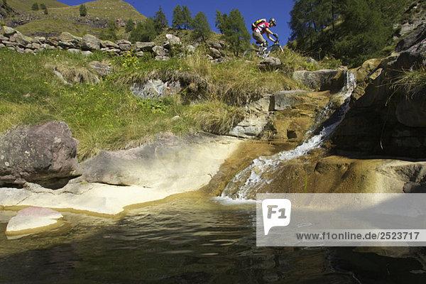 Mountainbikefahrer über einem Bergbach  fully_released
