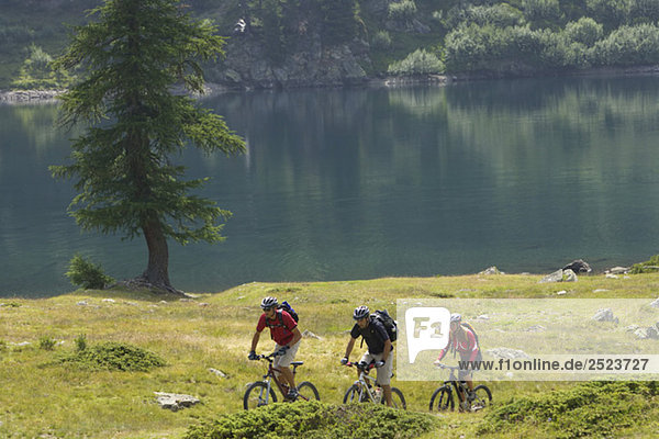 Drei Mountainbikefahrer fahren am Wasser  fully_released