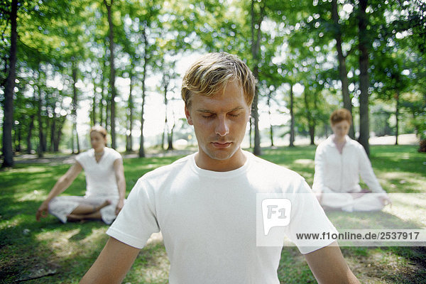 Menschen  die meditieren in Park